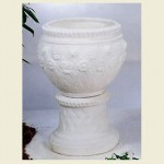 Large Concrete Pot with daisy flower design sitting on a concrete pedestal