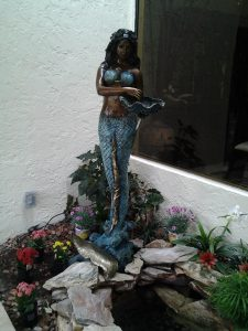 Statue of a Mermaid holding shell. The bronze statue is stained blue to make the mermaid stand out.